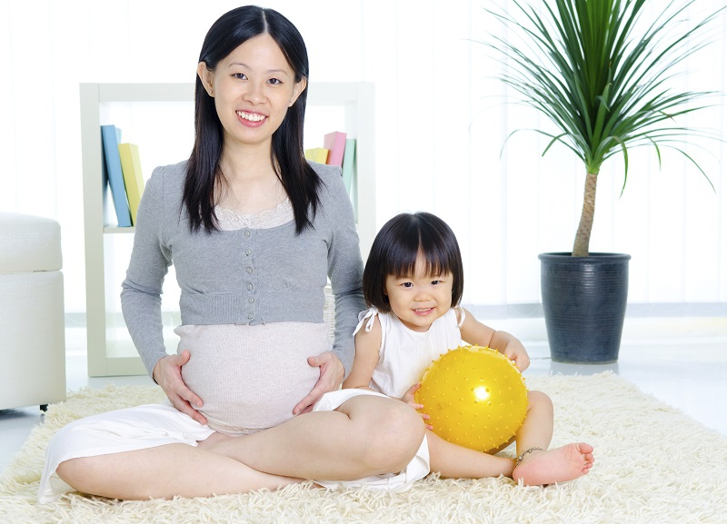 Smiling pregnant Asian woman with her daughter.