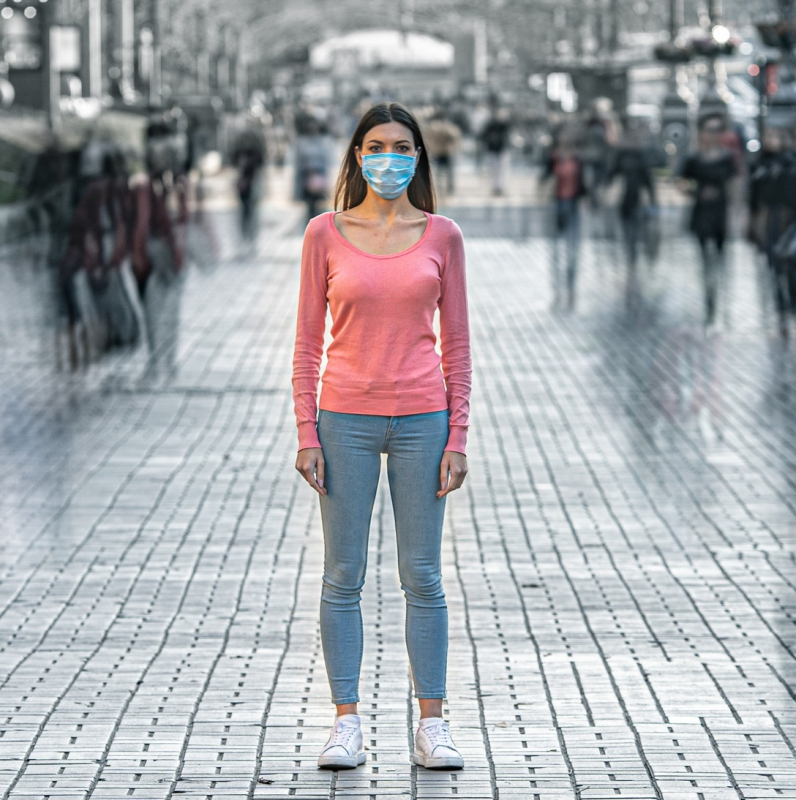 Woman wearing a mask to protect from COVID in the middle of a busy intersection.